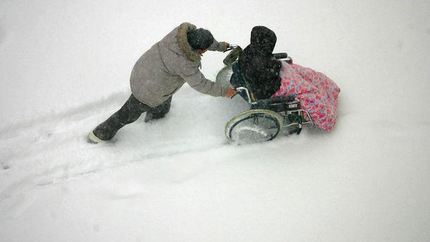 Man pushes wheelchair through the snow